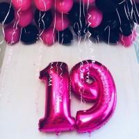 Розовые фольгированные цифры и чёрно-розовые шары под потолок