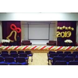 Красно-золотое оформление сцены школы с колокольчиком и гирляндой по краю сцены