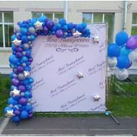 Большая фотозона с разнокалиберной гирляндой на стенде и фонтаном из шаров в синих тонах