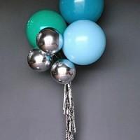Фонтан из сине-зеленых больших шаров и серебристых фольгированных сфер на гирлянде из дождика